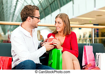 Man with gift for woman in mall