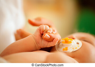 Baby gripping hand of mother