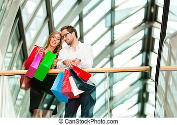 Man and woman in shopping mall with bags - Couple - man and...