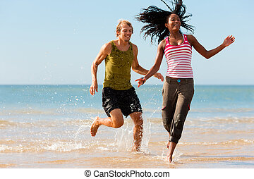 Sport couple jogging on the beach