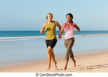 Sport couple jogging on the beach - Young sport couple -...