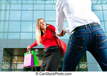 Woman dragging man into shopping mall - Woman wants to shop...