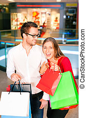 Man and woman in shopping mall with bags