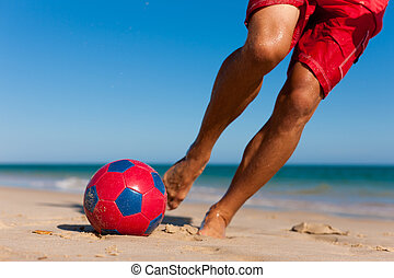 Man on beach playing soccer