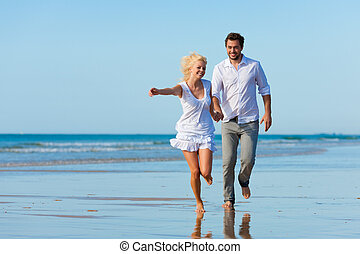 Couple on the beach running into glorious future