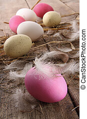 Colorful easter eggs with feathers on old table