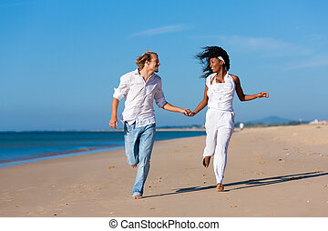 Couple walking and running on beach - Couple - black woman...