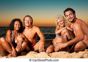 Four friends at sunset beach