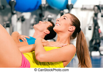 Sit-ups in gym for fitness - two people, man and woman,...