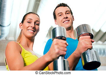Gym training with dumbbells - couple in the gym, rivaling...