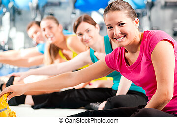 People in gym warming up stretching - Group of four people...