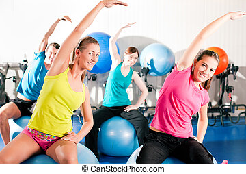 People in gym on exercise ball - Four people - man and women...