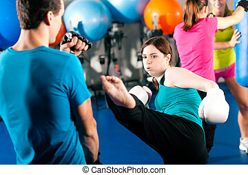 Female kick boxer with trainer in sparring