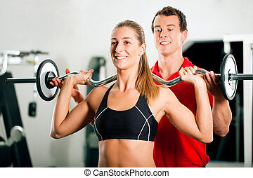 Woman with Personal Trainer in gym - Woman in gym with...