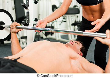 man in gym exercising with barbell