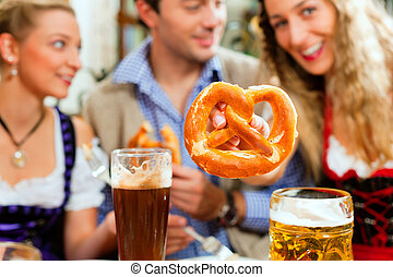 People with beer and pretzel in Bavarian pub