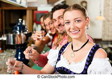 Clinking glasses with hard liquor - People in Bavarian...