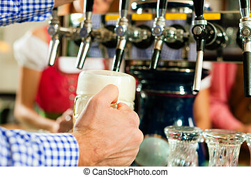 Man drawing beer from tap - Man drawing a beer from tap on a...