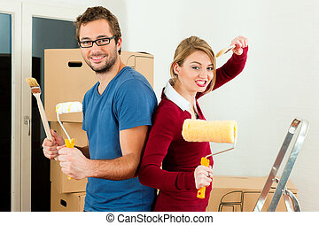 Young couple moving in a home or apartment, they are...