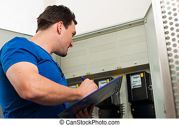 Technician reading the electricity meter to check...