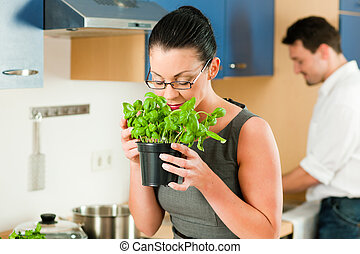 Couple cooking together in kitchen - Woman smells the aroma...