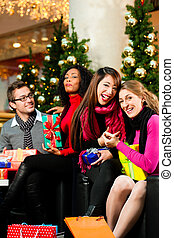 Friends with Christmas presents and bags in mall