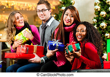 Friends with Christmas presents and bags in mall - Diversity...
