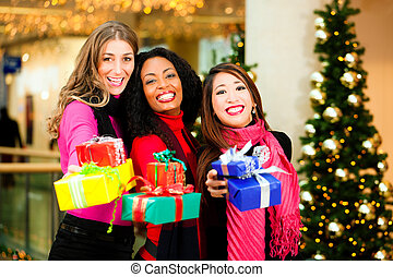 Friends Christmas shopping with presents in mall - Group of...