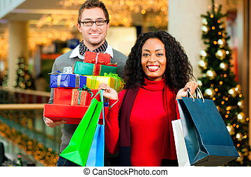 Couple Christmas shopping with presents in mall - Couple -...