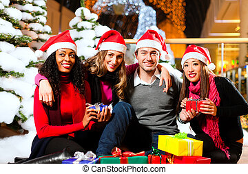 Friends Christmas shopping with presents in mall