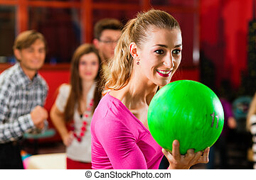 Friends bowling having fun - Group of four friends in a...