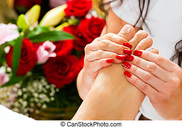 Woman in nail studio receiving foot massage - Woman...