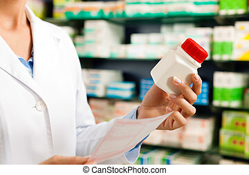 Female pharmacist in pharmacy with medicament - Female...