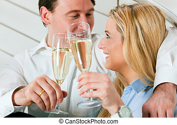 Business Couple at home with champagne