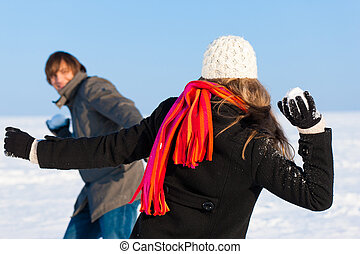 Couple having snowball fight - Couple - man and woman -...