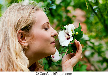 Woman in garden sniffing at flowers