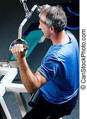 Senior man exercising in gym - Senior man in the gym lifting...