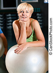 Senior Woman with fitness ball in gym