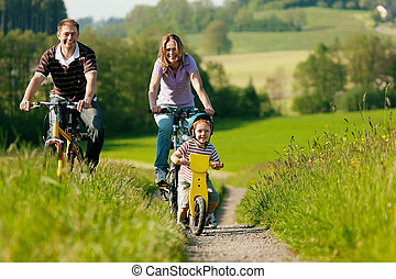Family riding bicycles in summer - Family on a trip with...