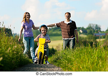 Active family in summer walking and bicycling - Family with...