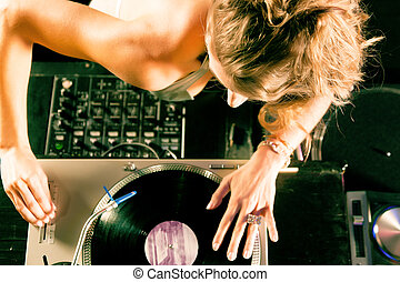 Female DJ at the turntable in Club - Female DJ at the...