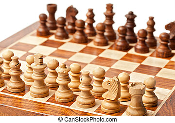 Wooden chess pieces on chessboard.