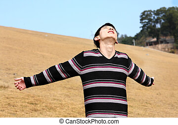 Carefree man standing in golden grass field being happy enjoying freetime