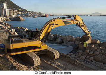 Working on the shore - A construction worker and a JCB...