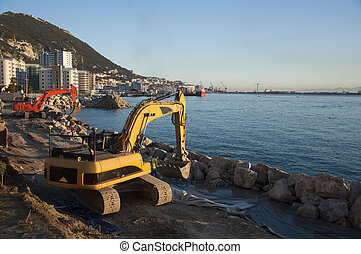 Red & Yellow Diggers - A red and yellow digger working in...