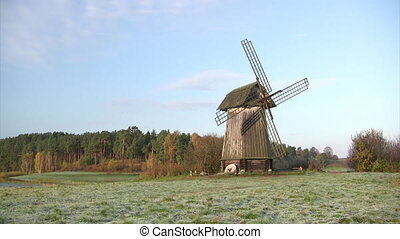 Old wooden windmill - Old wooden mill against autumn forest...