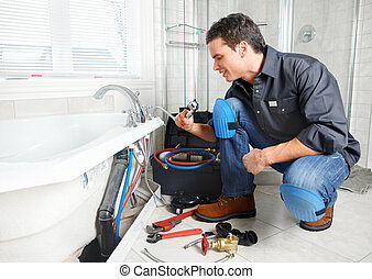 Plumber - Young plumber fixing a sink. Worker at kitchen