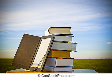 Stack of books with ebook reader outdoors laying on table
