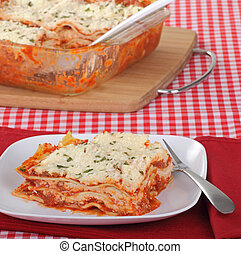Lasagna Dinner - Lasagna pasta on a plate with serving dish...