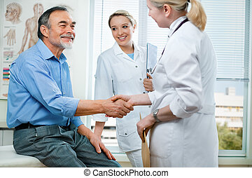 at the doctors office - doctor shakes hands with a patient